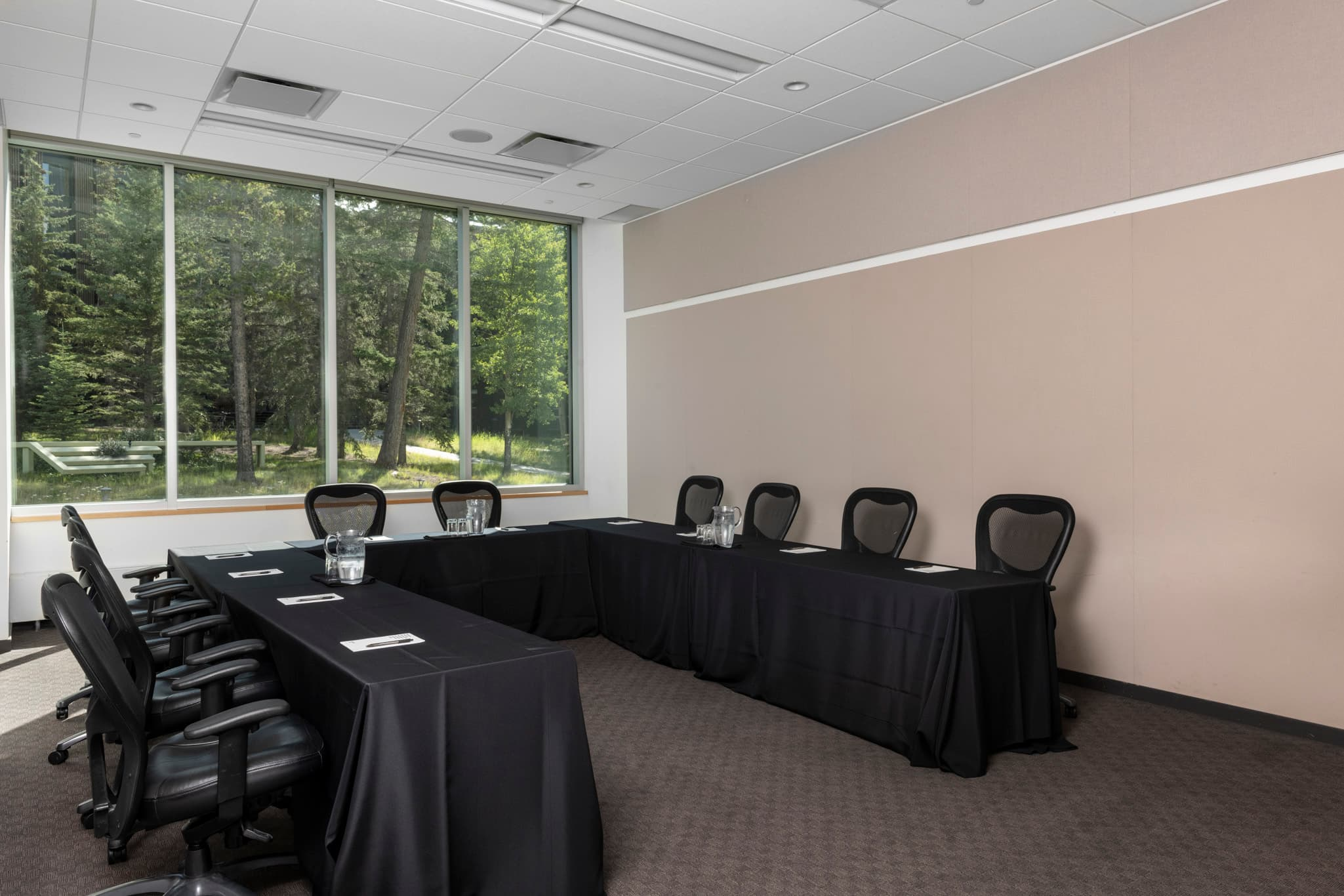 An open ended round table meeting room with a large window.