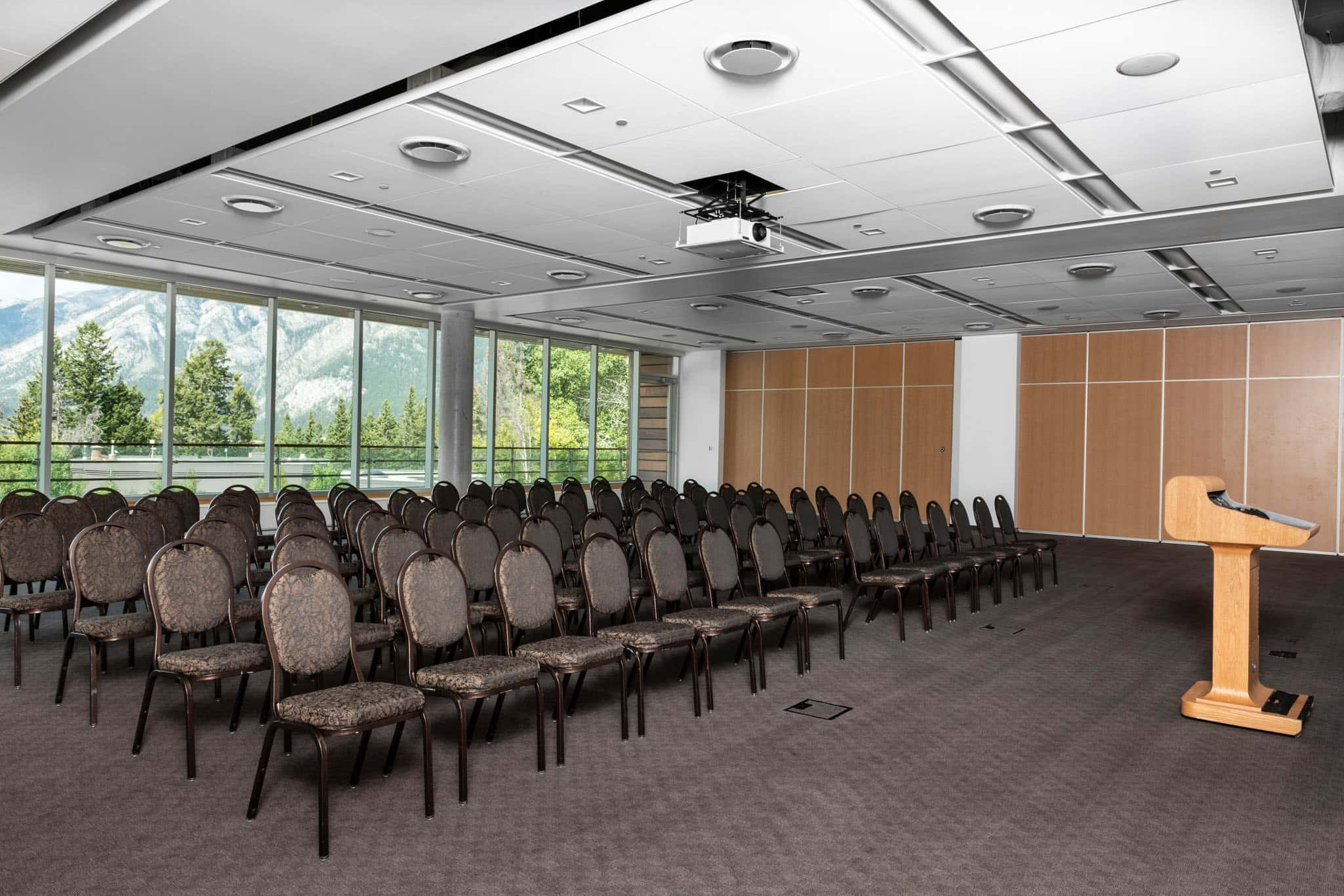 A meeting room set up for a presentation with a podium overlooking chairs.