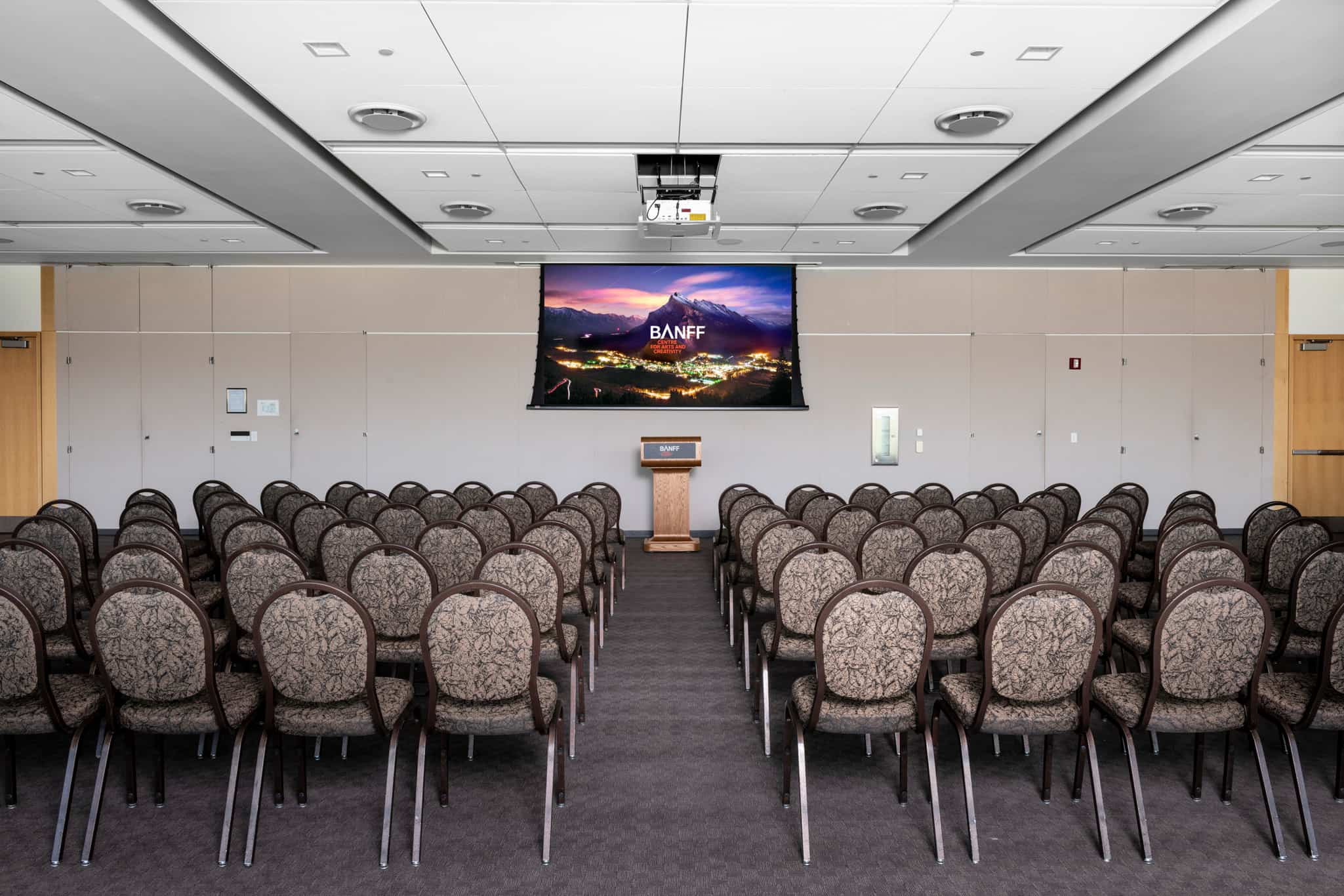 Smaller Presentation room equipped with a podium, screen and chairs.