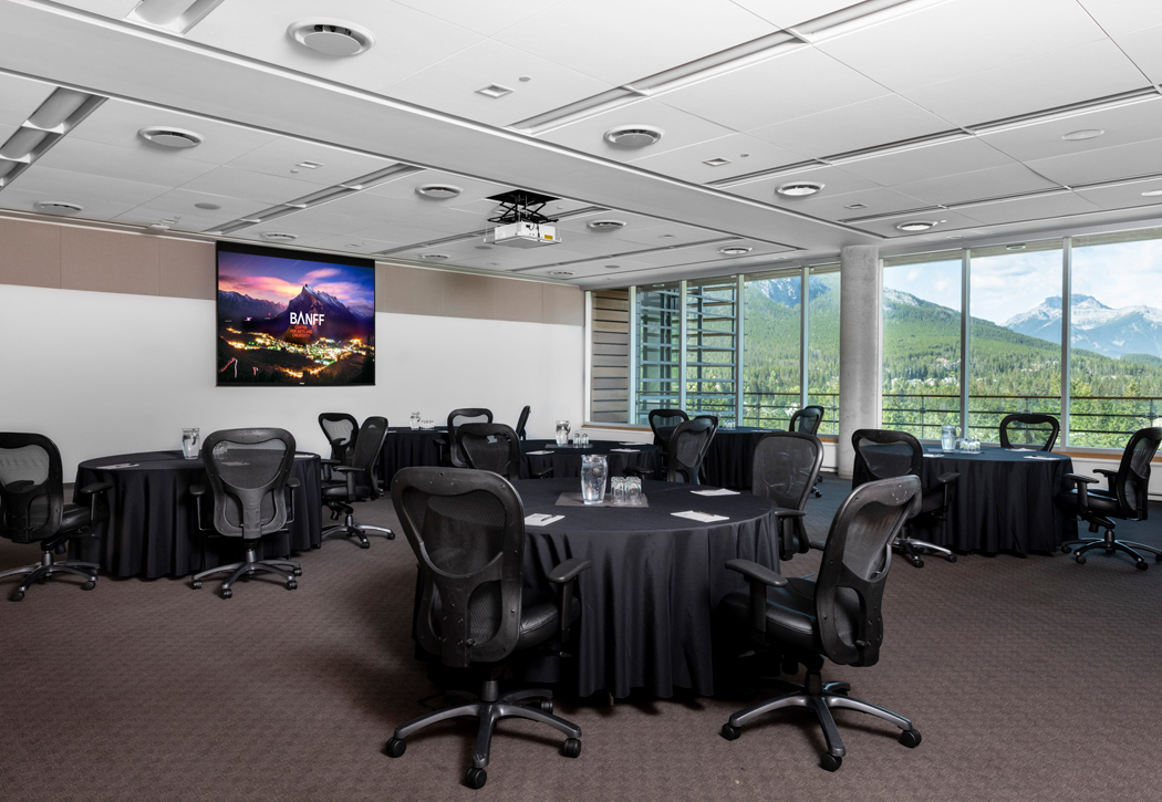 Meeting room with screens and roundtables.