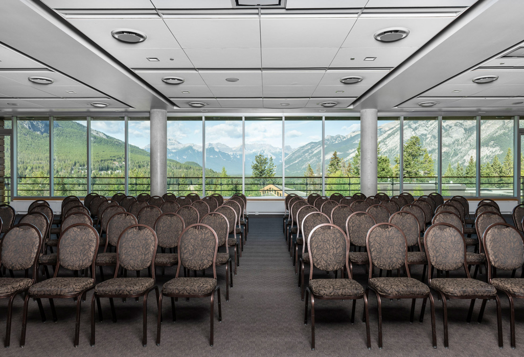An empty presentation room with a large window in the back.