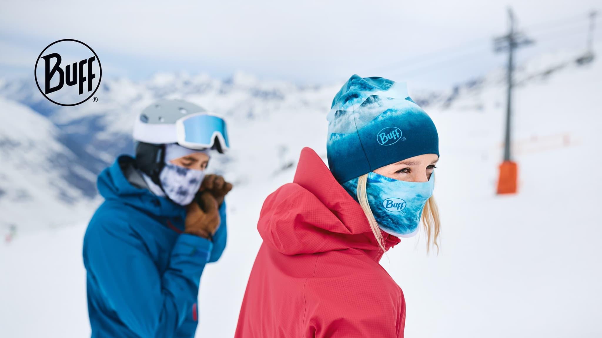 two people on ski hill wearing Buff