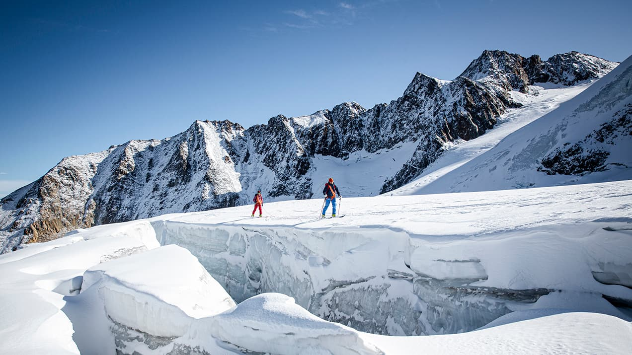 Two climbers walking along a glacier beside a large crevasse