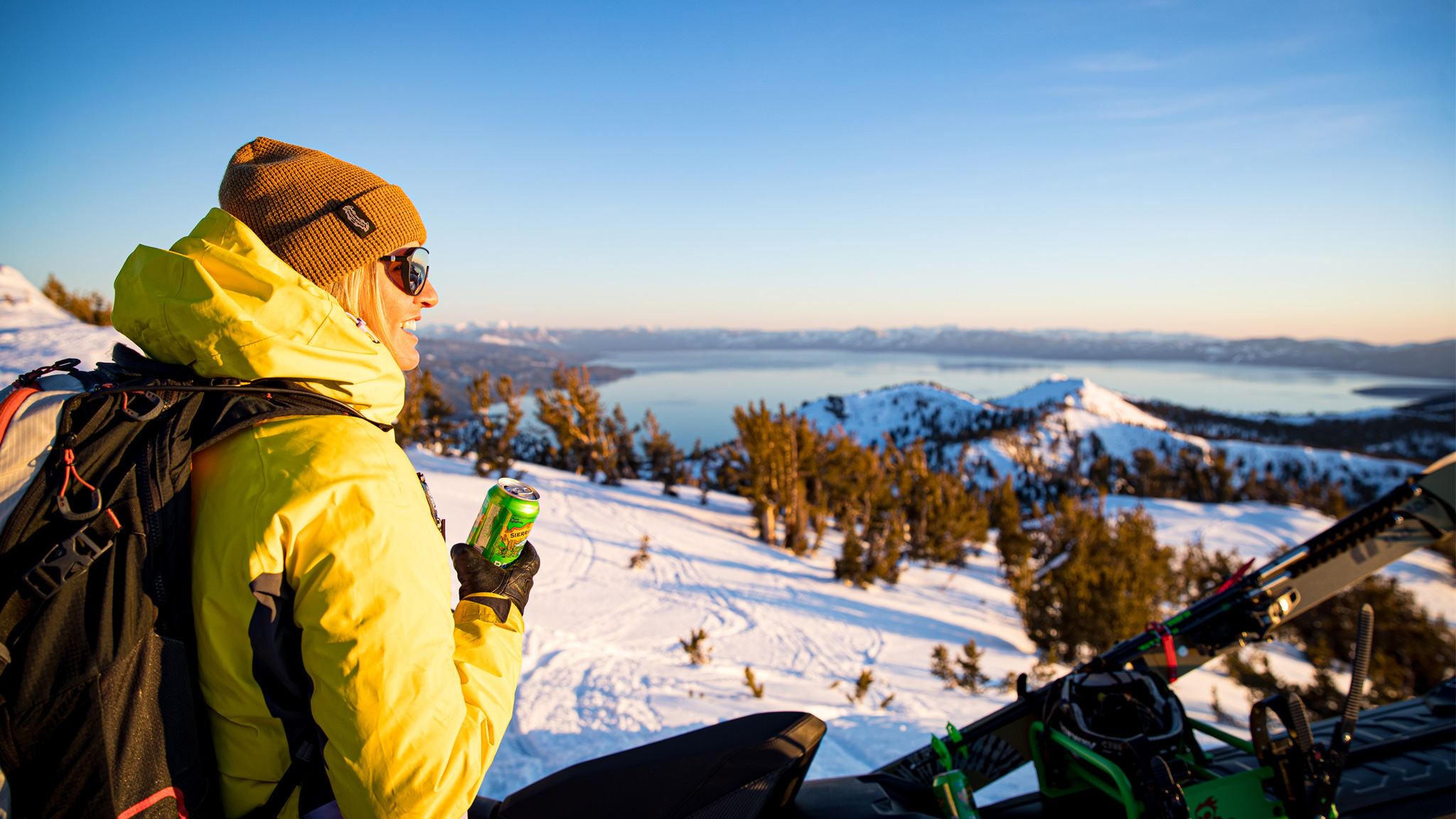 A skier sits on her snowmobile enjoying a beer watching the sunset.