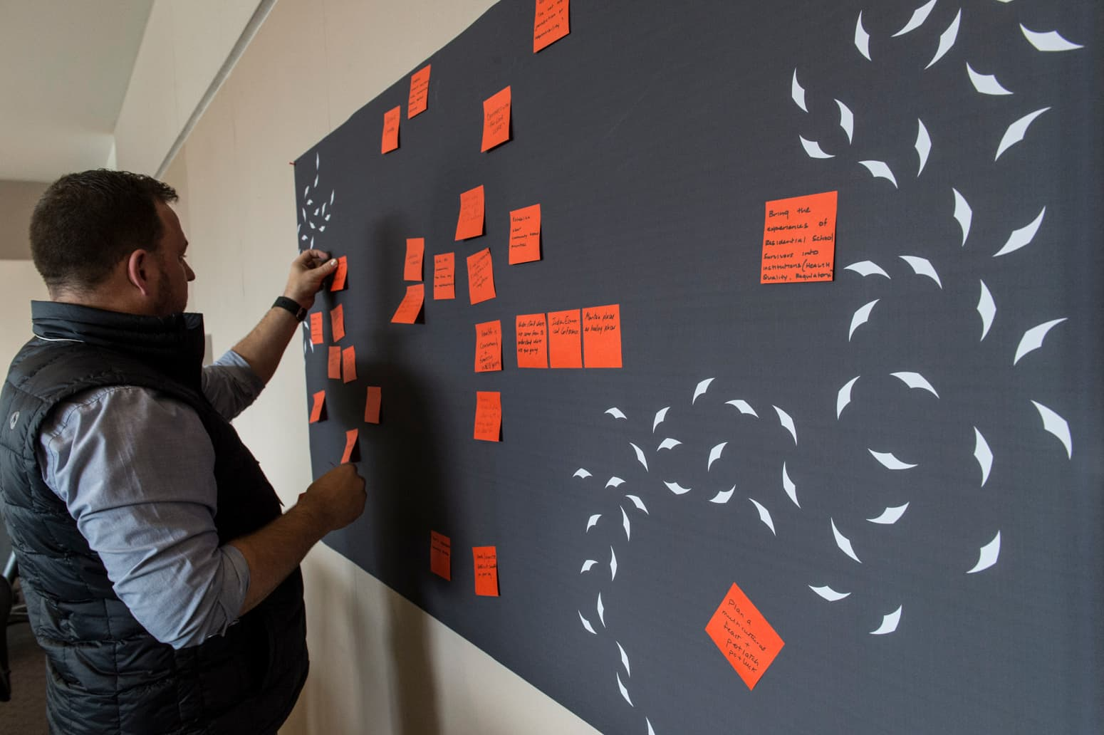 Truth and Reconciliation participant using sticky notes on a communal board