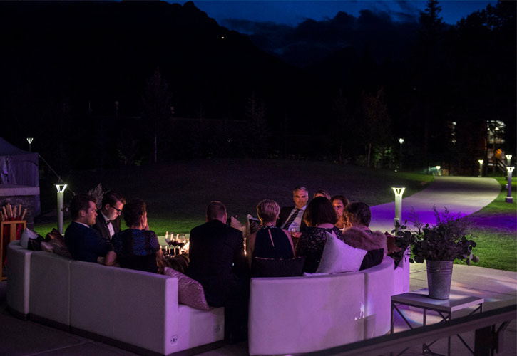 Guests gather around a fire at the Midsummer Ball event.