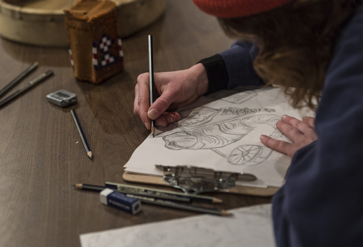 An artist sketches an animal drawing on a desk.