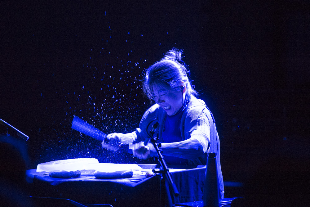 A woman lit with an overhead blue light beats a unique drum set.