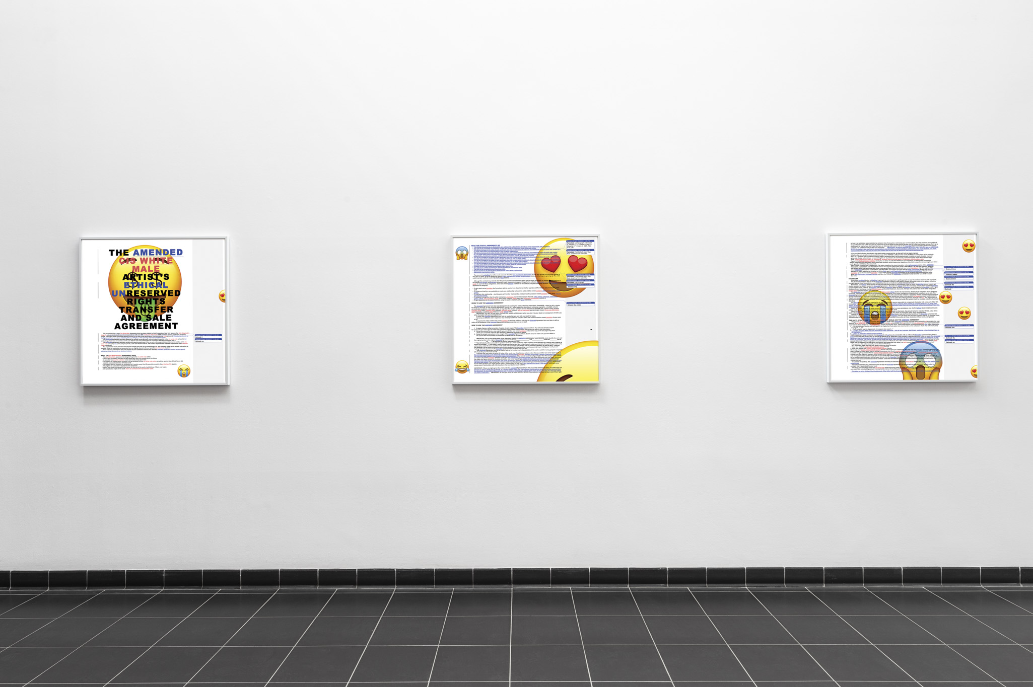 Three artworks line a hallway painted white. The artworks have white frames. The artworks feature a text document that shows edits, and a variety of emojis overlaying the text.