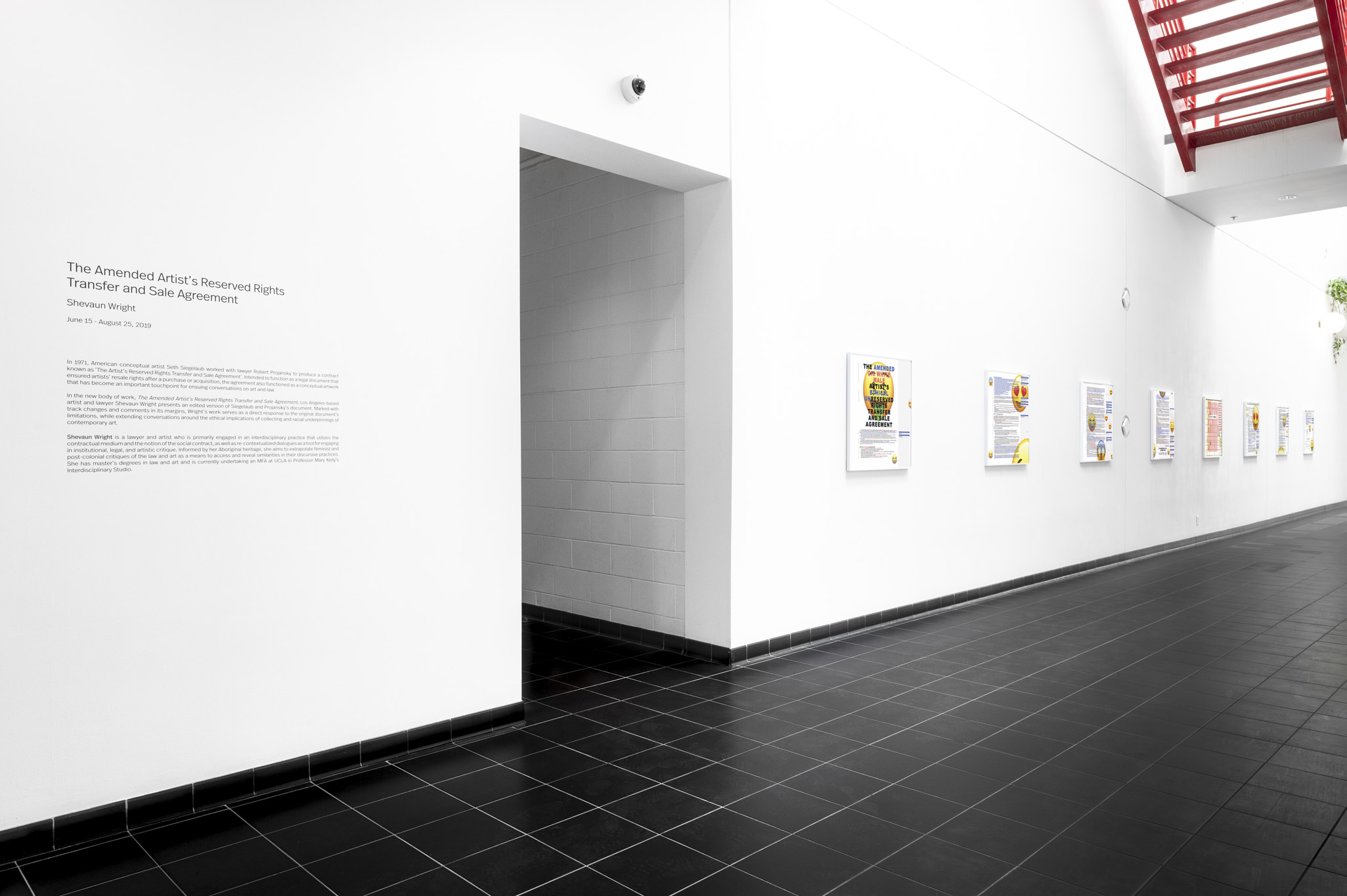 A long white hallway has text about the exhibition and then a series of artworks hung next to it.