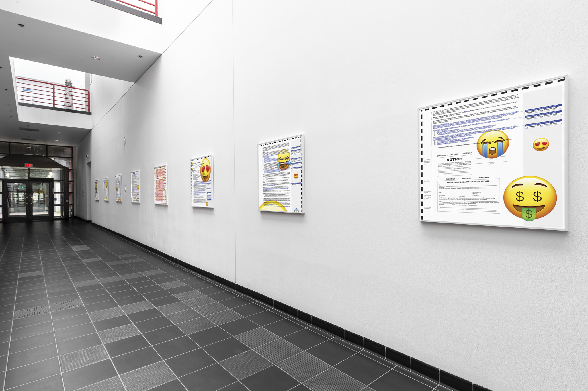 Eight artworks line a white hallway with black tile flooring. Each artwork is hung in a white frame and is a document with a variety of emojis overlaying the text.