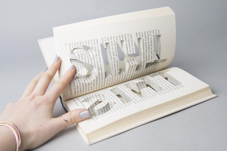 Image of hand holding open an artists' book.