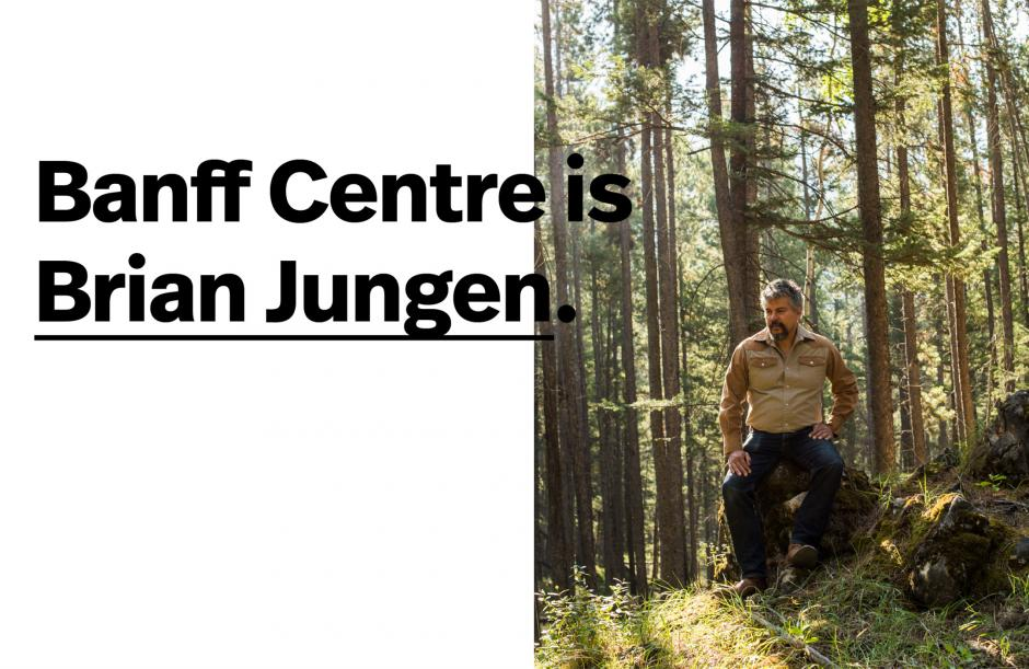 Brian Jungen, visual artist sits in a forest on a sunny day.