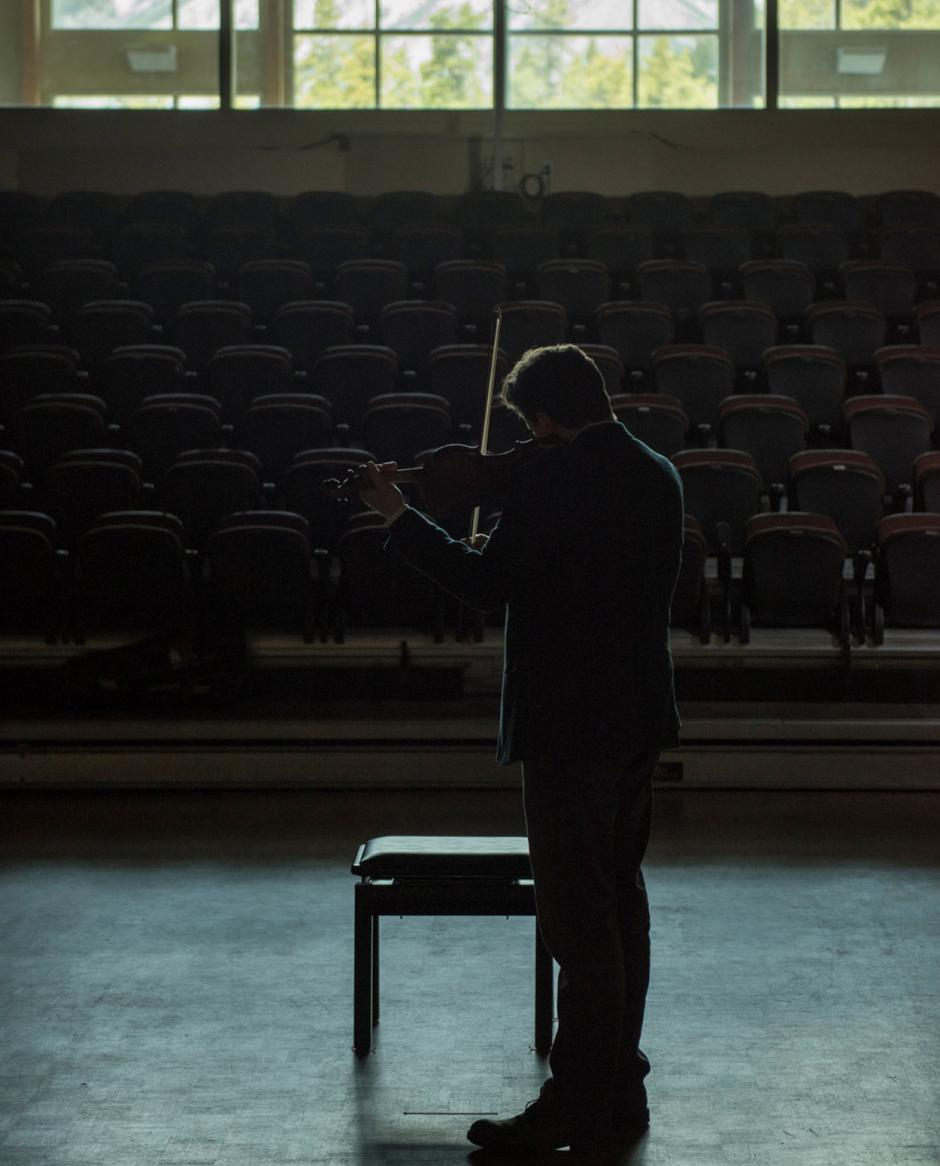 Solo Violinist on a darkly lit stage of an empty theatre.