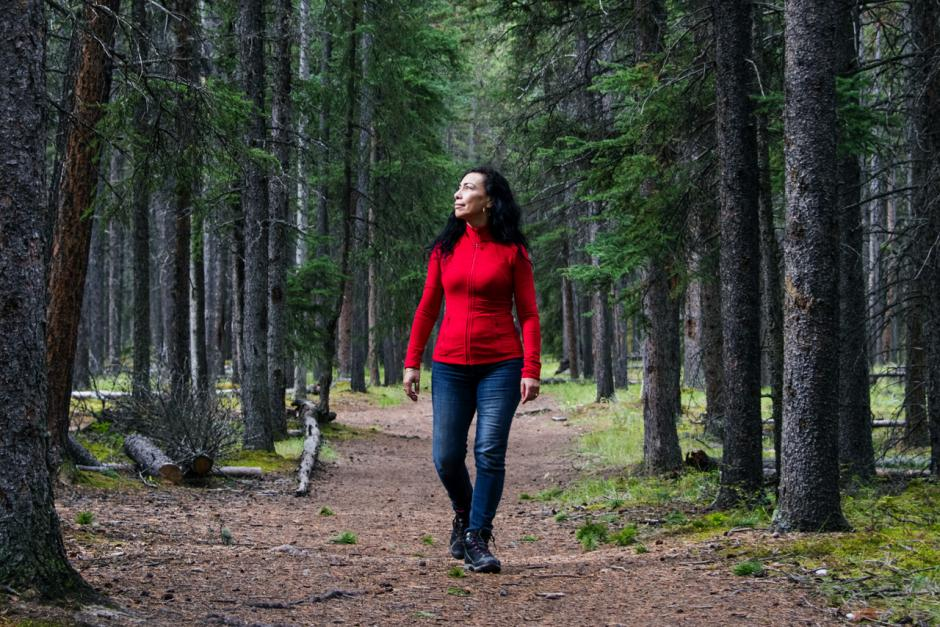 Carmen Aguirre walks through a forest surrounded by trees.