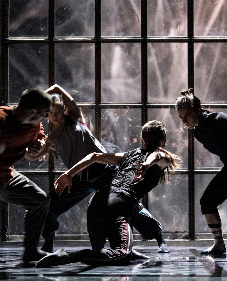 Four dancers performing on a dark stage.