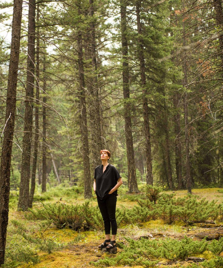 Emily Molnar stands in a forest surrounded by lush tall tress.
