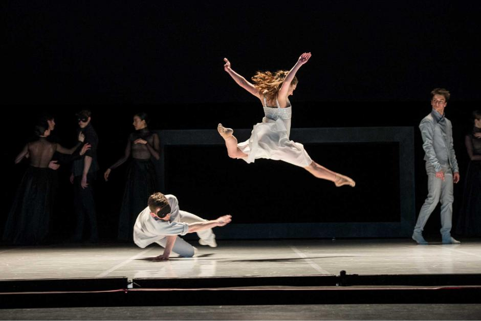 Romeo + Juliet ballet performance on a black stage. Two dancers in the forefront with a number in the background.
