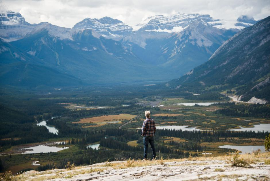 Joel Ivany stands atop a mountain overlooking a mountain range.
