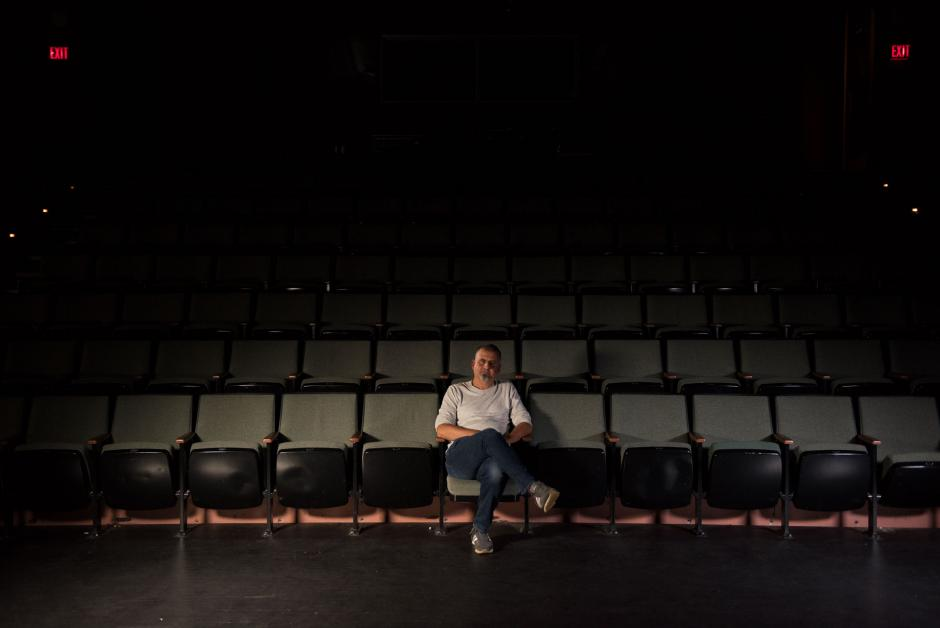 Marcus Youssef sitting in a dark theatre.