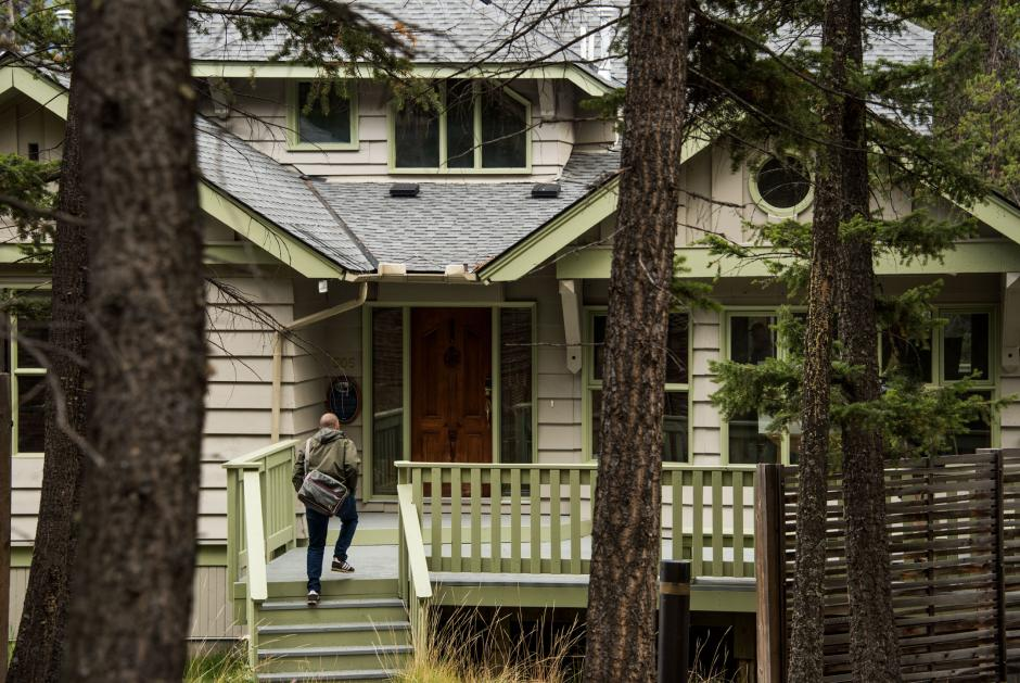 Man walking into a house in the woods.