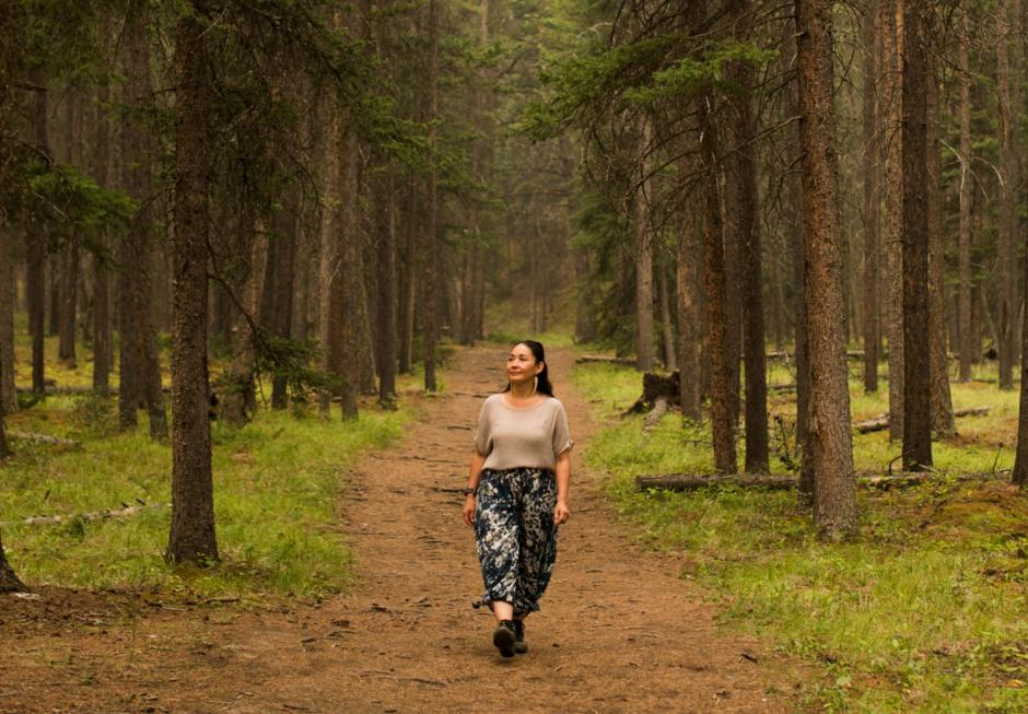 Artist Reneltta Arluk walking through the forest on a rainy day.
