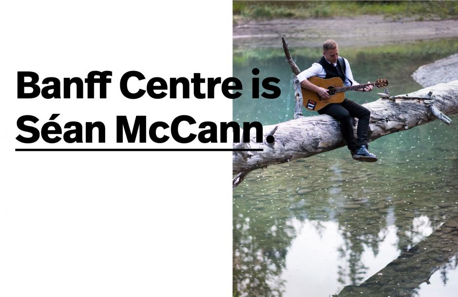 Musician Sean McCann sitting in nature tuning his guitar.