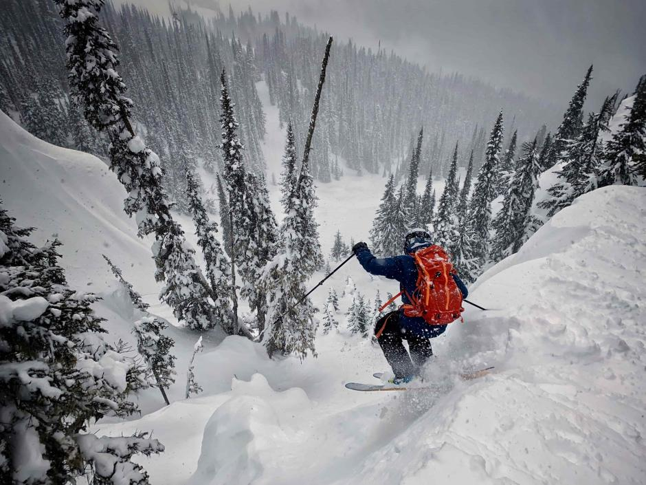 A skier is dropping off a cliff into deep powder