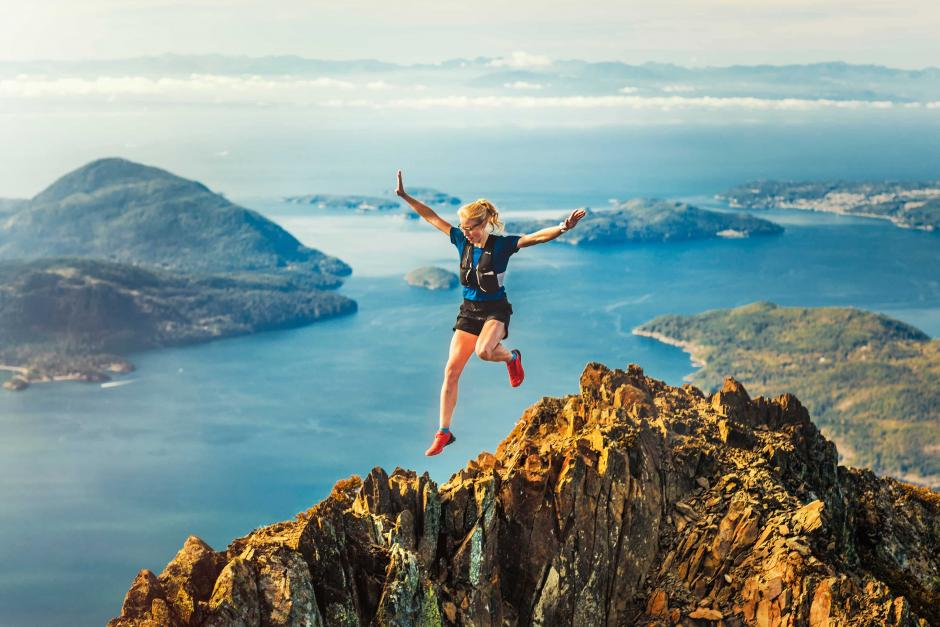 A female athlete is leaping down the mountain ridge.