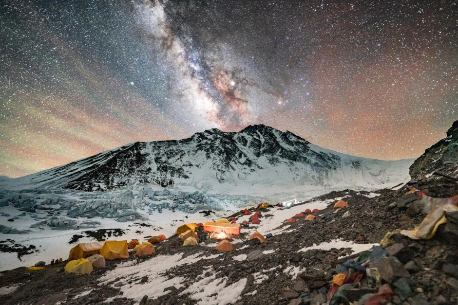Tents scattered across a snowy mountain peak with a star filled sky.
