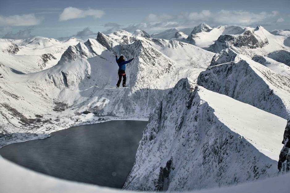 An athlete is walking on a slackline amongst snowcapped mountain peaks.