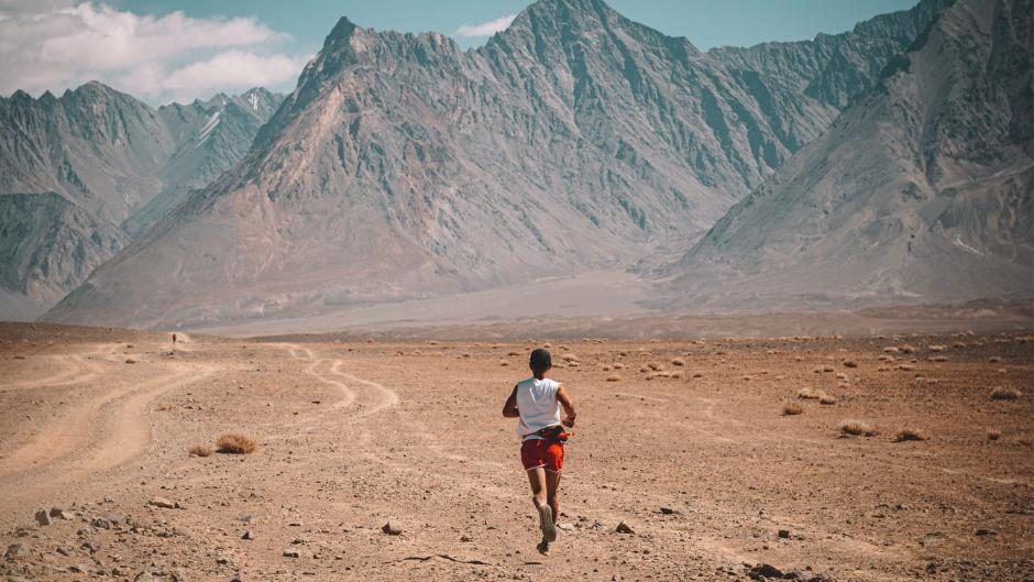 Athlete runs across sand and dirt in a dry mountain range.