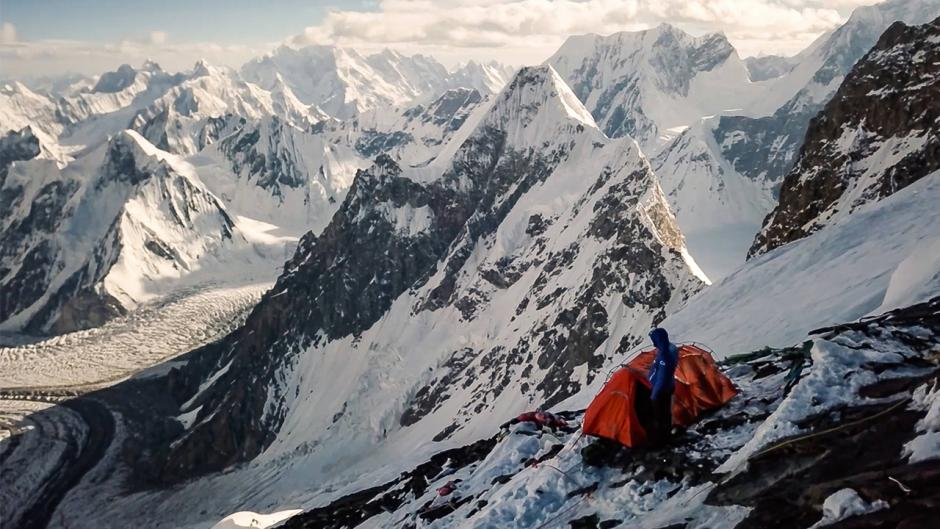 A adventurer standing outside his tent overlooking a snow filled mountain range.
