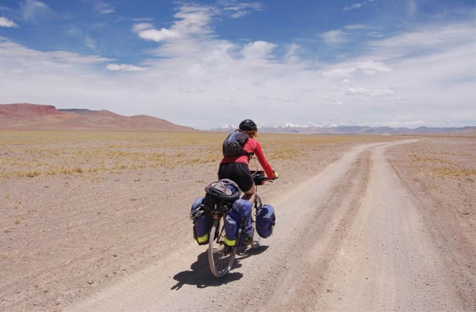 Female cyclist travelling down a dirt road