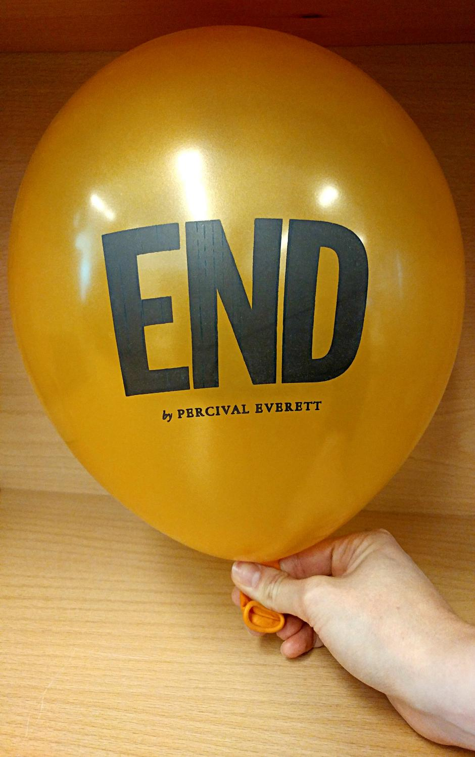 "A golden balloon inflated with the text, ""End by Percival Everett"" printed on it."