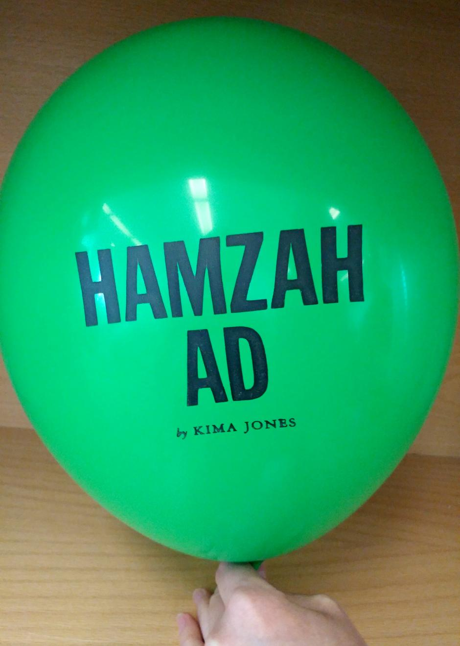 "A green balloon inflated with the text, ""Hamzah Ad by Kima Jones"" printed on it."