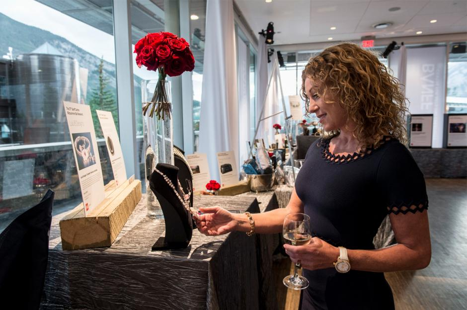 Gala attendee checks out silent auction items at Midsummer Ball.