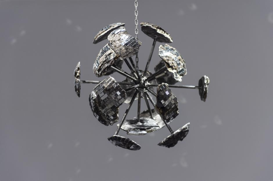 A disco ball sculpture that has been broke into fragments exploding outward but is held together by rods extending from the centre.