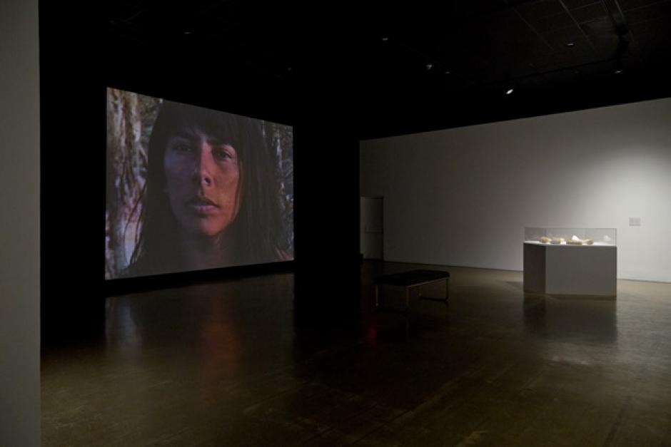 A dark gallery has a diffuse spotlight on an artistic stand, a screen in the background shows the face of an indigenous woman.