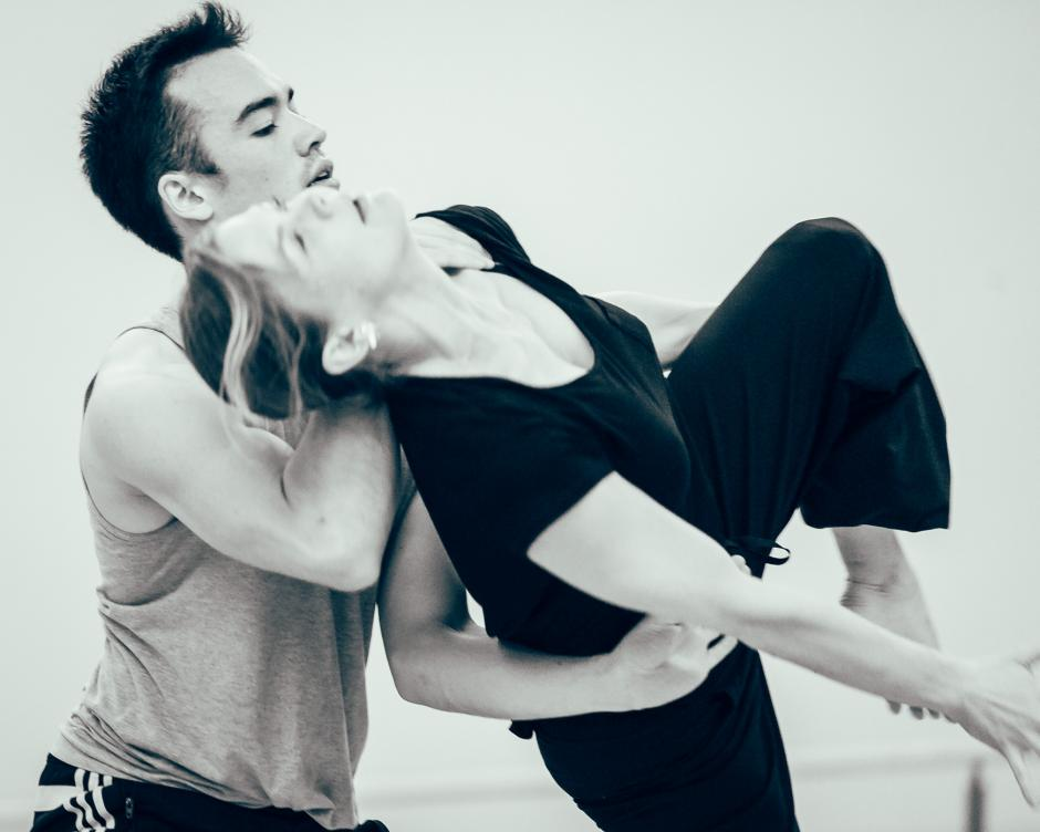 Two dancers engage in a position where one balances on the others arms with legs moving.