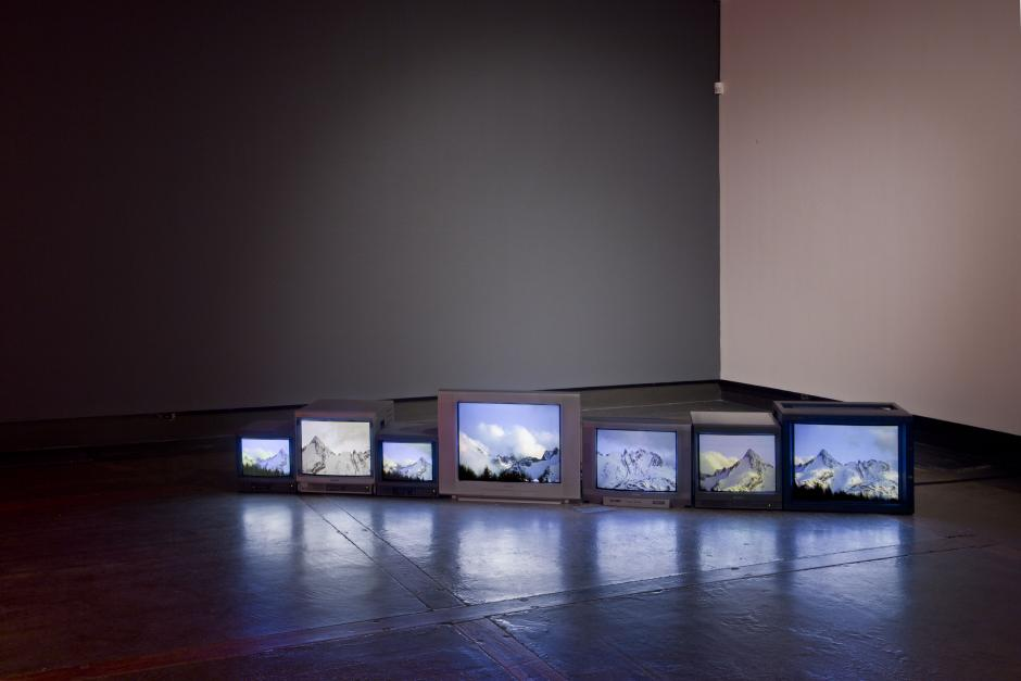 A line of 7 retro screens display a mountain landscape in an empty room.