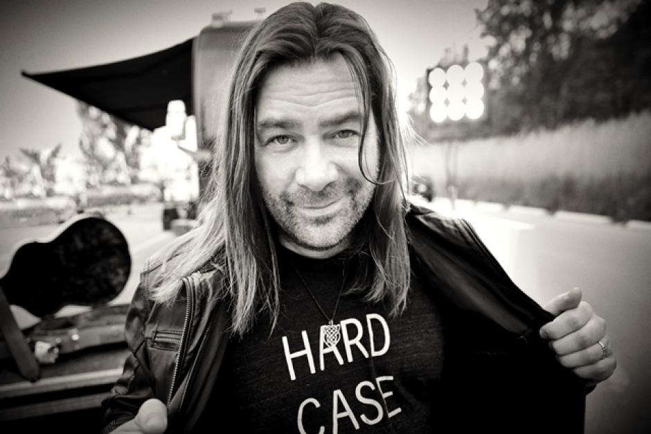 "Alan Doyle holds the left and right sippers of his black leather jacket open displaying a t-shirt with the words ""HARD CASE."""