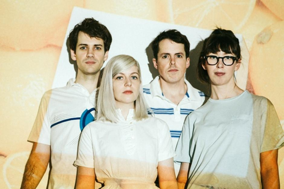 The four members of the band Alvvays stand with a projection of oranges overlaying them.