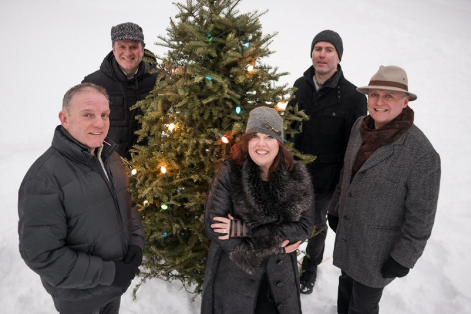 The Barra MacNeils stand around a Christmas tree in the snow.