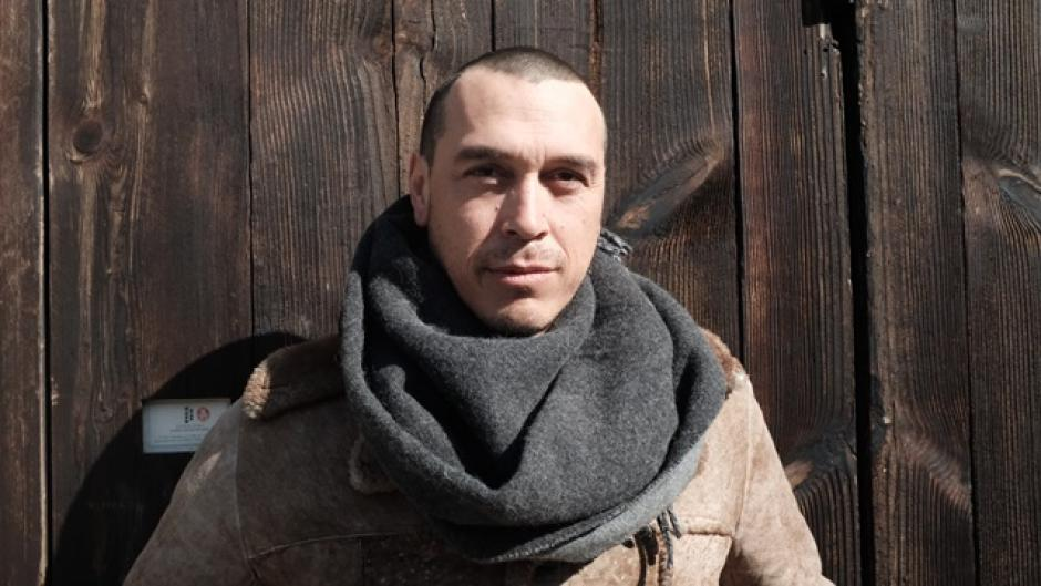 Artist Cannupa Hanska Luger stands in front a wooden wall, he is wearing a scarf and winter clothes.