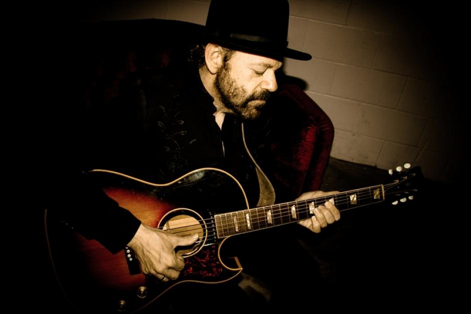 Colin Linden plays an acoustic guitar.
