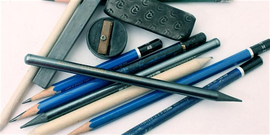 Pencils and other mark making materials sit atop paper.