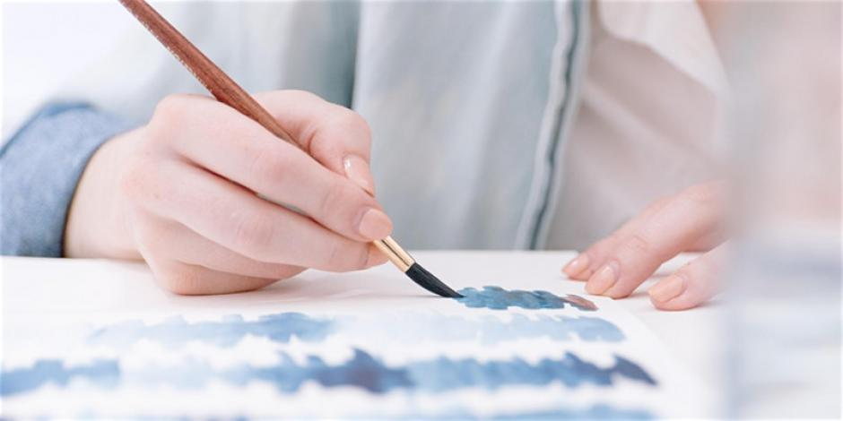 hands hold paper and a brush while making watercolor art.
