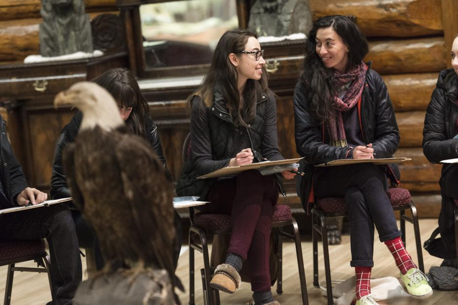 With a taxidermy eagle in the foreground participants are seated around it drawing.