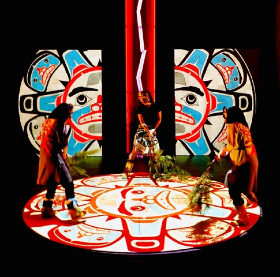 Three dancers perform on a stage dramatically lit with indigenous iconography.